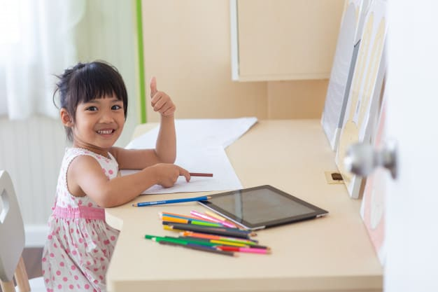 Happy child with her effective and productive home based learning corner