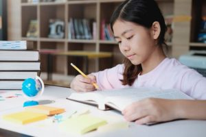 Singaporean girl revises for her PSLE examination at home with attention