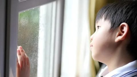 Boy looking out of the winodw in the middle of an online test to calm himself down and reduce exam anxiety