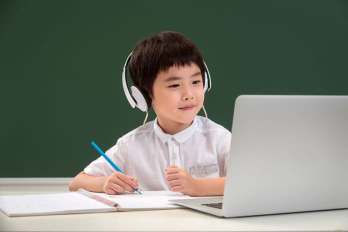 Boy in Singapore doing his home based learning using a computer