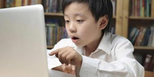 Child looking at the computer as he engrosses in online learning and online tuition from SmileTutor